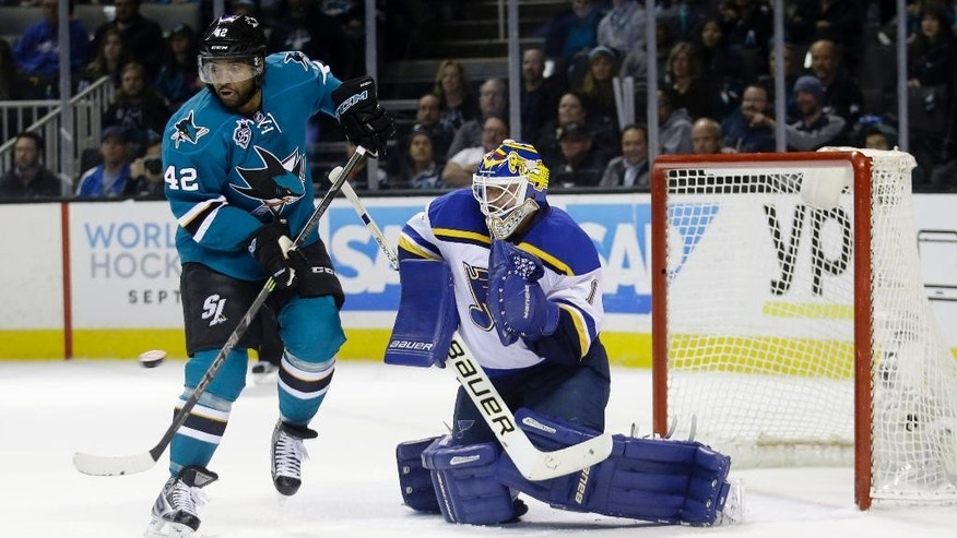 San Jose Sharks' Joel Ward (42) works near the goal next to St. Louis Blues goalie Brian Elliott during the first period of an NHL hockey game Tuesday, March 22, 2016, in San Jose, Calif. (AP Photo/Marcio Jose Sanchez)
