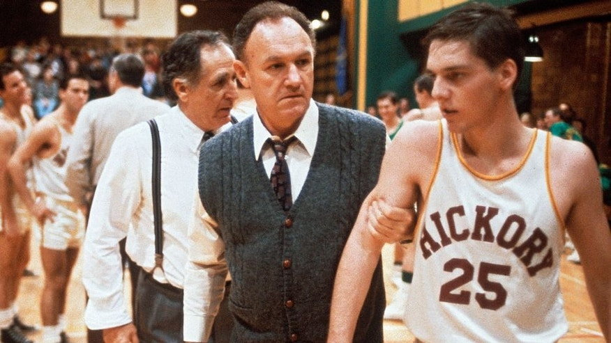 """The coach Norman Dale, played by the American actor Gene Hackman, grasps to the arm of a basketball player before a match and rebukes him, in a scene from the engaging dramatic movie Hoosiers. USA, 1986. (Photo by Mondadori Portfolio via Getty Images)"""