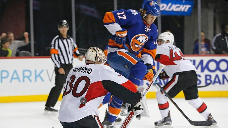 New York Islanders left wing Matt Martin (17) leaps as the puck careens off the back of Ottawa Senators goalie Andrew Hammond (30) in the second period of an NHL hockey game in New York, Wednesday, March 23, 2016. Martin scored the second of three Islanders goals in the second period. (AP Photo/Kathy Willens)