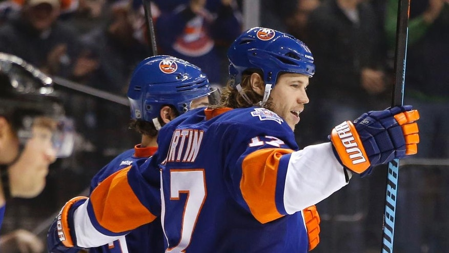New York Islanders left wing Matt Martin (17) celebrates with a teammate after scoring the second of three Islanders goals in the second period of an NHL hockey game against the Ottawa Senators in New York, Wednesday, March 23, 2016. (AP Photo/Kathy Willens)