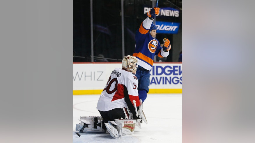 New York Islanders left wing Matt Martin (17) looks toward his teammates as he celebrates a goal as the puck swirls behind Ottawa Senators goalie Andrew Hammond (30) in the second period of an NHL hockey game in New York, Wednesday, March 23, 2016. Martin scored the second of three Islanders goals in the second period. (AP Photo/Kathy Willens)