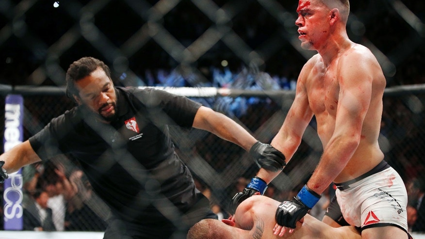 Referee Herb Dean stops the fight shortly after Nate Diaz defeats Conor McGregor in a second round submission victory during their UFC 196 welterweight mixed martial arts match, Saturday, March 5, 2016, in Las Vegas.