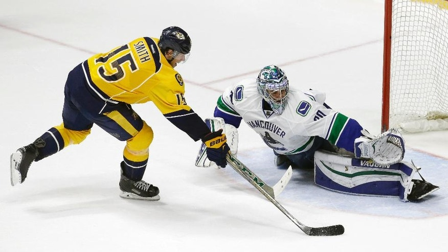 Nashville Predators center Craig Smith (15) scores against Vancouver Canucks goalie Ryan Miller during the shootout in an NHL hockey game Thursday, March 24, 2016, in Nashville, Tenn. The Predators won 3-2. (AP Photo/Mark Humphrey)