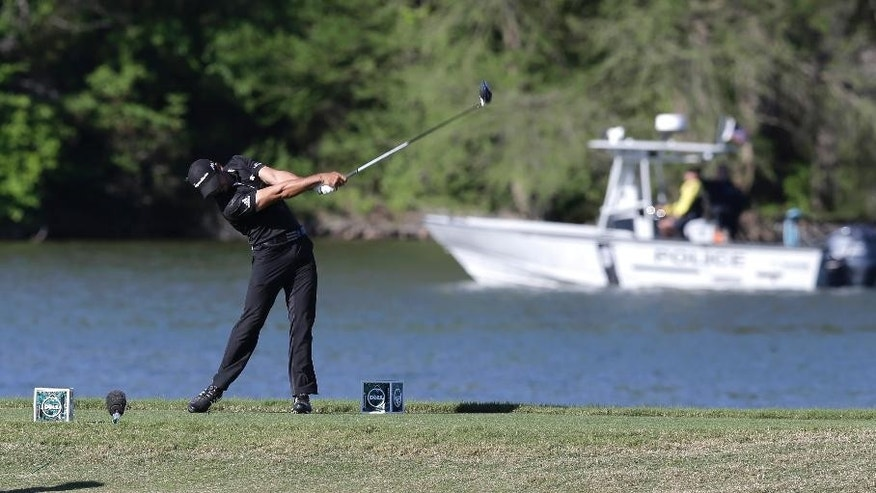 Jason Day, of Australia, hits his tee shot on the 14th hole as a boat passes on Lake Austin during round-robin play against Thongchai Jaidee at the Dell Match Play Championship golf tournament at Austin County Club, Thursday, March 24, 2016, in Austin, Texas. (AP Photo/Eric Gay)