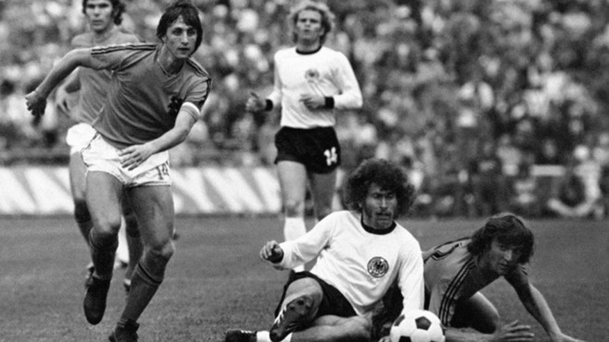 This is a July 7, 1974 file photo of Dutch forward Johan Cruyff, left, runs past German defender Paul Breitner, sitting on the pitch during the final of the Soccer World Cup at the Olympic Stadium in Munich, Germany. Dutch soccer great Johan Cruyff, who revolutionized the game with the concept of 'Total Football,' died Thursday March 24, 2016. He was 68. (AP Photo)