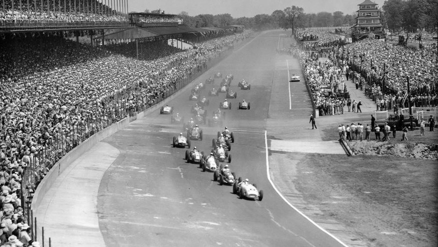 FILE - In this May 31, 1954, file photo, thirty-three competitors approach the first curve of the Indianapolis Motor Speedway in the 38th running of the Indianapolis 500 auto race  in Indianapolis, Ind. Pole winner Jack McGrath, right, driving a Hinkle Special, is leading.  (AP Photo/File)