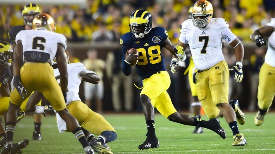 Sep 7, 2013; Ann Arbor, MI, USA; Michigan Wolverines quarterback Devin Gardner (12) runs the ball during the third quarter against the Notre Dame Fighting Irish at Michigan Stadium. Mandatory Credit: Andrew Weber-USA TODAY Sports