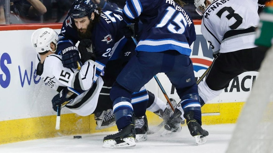 Winnipeg Jets' Chris Thorburn (22) takes down Los Angeles Kings' Andy Andreoff (15) as Jets' Matt Halischuk (15) and Kings' Brayden McNabb (3) scramble for the loose puck during the second period of an NHL hockey game Thursday, March 24, 2016,  in Winnipeg, Manitoba. (John Woods/The Canadian Press via AP)