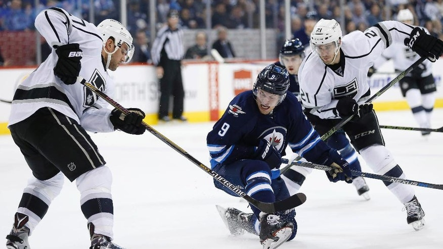 Winnipeg Jets' Andrew Copp (9) attempts to move between Los Angeles Kings' Alec Martinez (27) and Nick Shore (21) during the second period of an NHL hockey game Thursday, March 24, 2016,  in Winnipeg, Manitoba. (John Woods/The Canadian Press via AP)