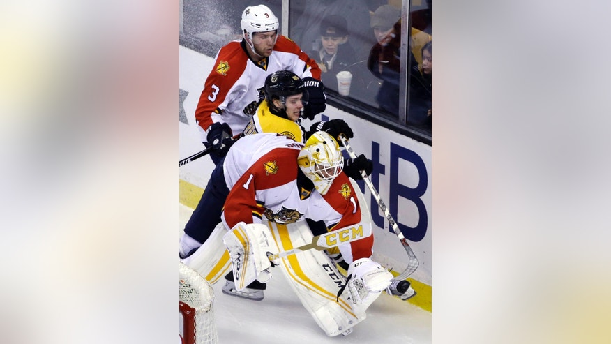 Boston Bruins left wing David Pastrnak is sandwiched between Florida Panthers defenseman Steven Kampfer (3) and goalie Roberto Luongo (1) against the boards behind the goal in the third period of an NHL hockey game, Thursday, March 24, 2016, in Boston. The Panthers won 4-1. (AP Photo/Elise Amendola)