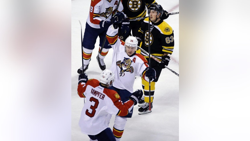 Florida Panthers left wing Jussi Jokinen (36) celebrates his goal with teammate Steven Kampfer (3) as Boston Bruins left wing Brad Marchand (63) looks on in the third period of an NHL hockey game, Thursday, March 24, 2016, in Boston. The Panthers won 4-1. (AP Photo/Elise Amendola)