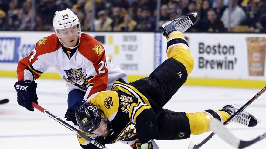 Boston Bruins defenseman Kevan Miller (86) is upended as he chases the puck against Florida Panthers left wing Jiri Hudler (24) in the second period of an NHL hockey game, Thursday, March 24, 2016, in Boston. (AP Photo/Elise Amendola)