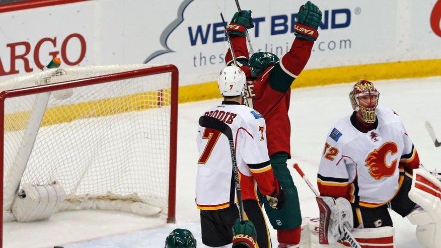 Minnesota Wild's Zach Parise, with hands up, celebrates his third goal for the hat trick against Calgary Flames goalie Niklas Backstrom, right, of Finland in the first period of an NHL hockey game, Thursday, March 24, 2016, in St. Paul, Minn. (AP Photo/Jim Mone)