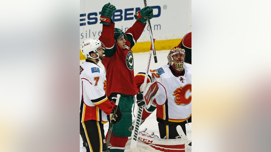 Minnesota Wild�s Zach Parise, center, celebrates his third goal for the hat trick against Calgary Flames goalie Niklas Backstrom, right, of Finland in the first period of an NHL hockey game, Thursday, March 24, 2016, in St. Paul, Minn. (AP Photo/Jim Mone)
