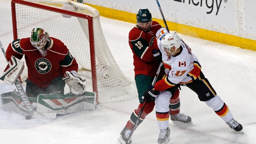 Minnesota Wild goalie Devan Dubnyk, left, stops a shot by Calgary Flames' Lance Bouma, right, as Wild's Thomas Vanek of Austria keeps him at bay in the first period of an NHL hockey game, Thursday, March 24, 2016, in St. Paul, Minn. (AP Photo/Jim Mone)