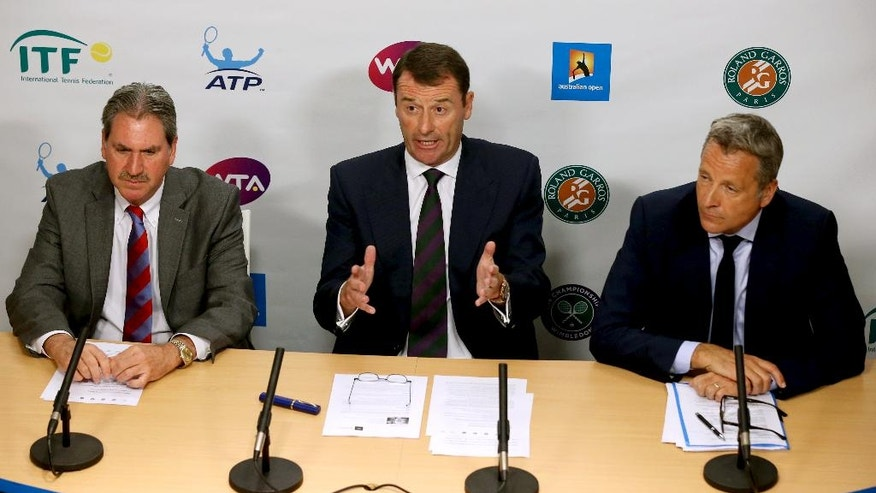 FILE - This is a Wednesday, Jan. 27, 2016 file photo of Wimbledon Chairman Philip Brook,  center,  speaks, along with ATP Executive Chairman and President Chris Kermode, right, and International Tennis Federation President David Haggerty, left, during a press conference at the Australian Open tennis championships in Melbourne, Australia. In his first six months as president of the International Tennis Federation, David Haggerty has had anything but a quiet period to settle into his new job. Not with allegations of match-fixing and corruption, the Maria Sharapova doping case and disputes over prize money buffeting the sport.  (AP Photo/Rick Rycroft, File)