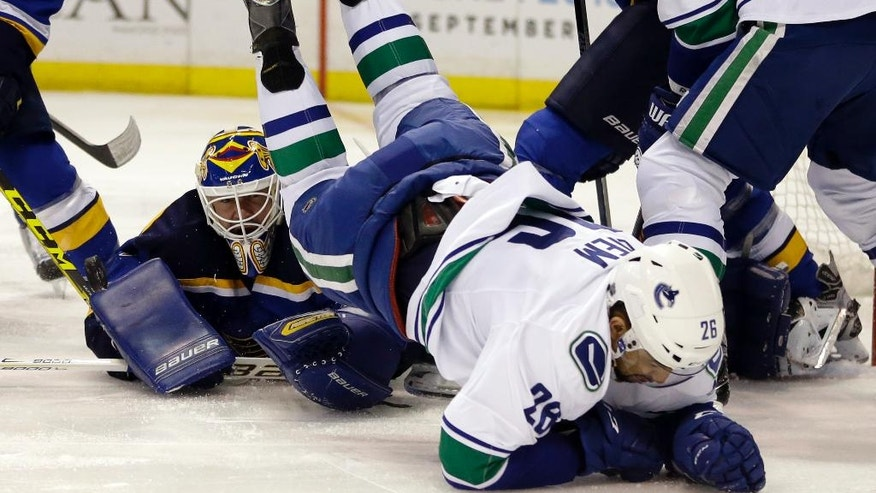 Vancouver Canucks' Emerson Etem, right, flips over St. Louis Blues goalie Brian Elliott while chasing after a loose puck during the first period of an NHL hockey game Friday, March 25, 2016, in St. Louis. (AP Photo/Jeff Roberson)