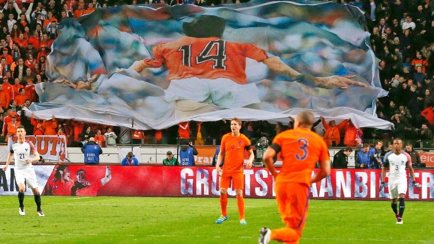 A banner with a picture of deceased legendary soccer player Johan Cruyff who played with number 14, is seen after players of the Dutch and French soccer squads observed a minute of silence in the 14th minute of the game during the international friendly soccer match between The Netherlands and France at the ArenA stadium in Amsterdam, Netherlands, Friday, March 25, 2016. (AP Photo/Peter Dejong)