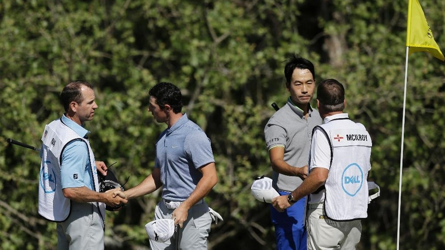 Rory McIlroy of Northern Ireland, second from left, and Kevin Na, second from right, and their caddies exchange hand shakes following a sudden-death playoff during round-robin play at the Dell Match Play Championship golf tournament at Austin County Club, Friday, March 25, 2016, in Austin, Texas. McIlroy won the match. (AP Photo/Eric Gay)