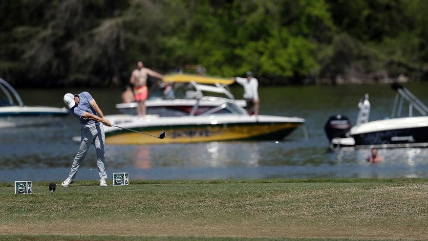 Rory McIlroy of Northern Ireland hits his tee shot on the 14th hole along Lake Austin during round-robin play against Kevin Na at the Dell Match Play Championship golf tournament at Austin County Club, Friday, March 25, 2016, in Austin, Texas. (AP Photo/Eric Gay)