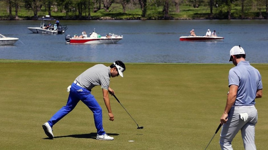 Kevin Na, left, reaches for his ball as Rory McIlroy of Northern Ireland, right, gets set to putt on the 14th green during round-robin play at the Dell Match Play Championship golf tournament at Austin County Club, Friday, March 25, 2016, in Austin, Texas. Rory McIlroy won the match in a sudden-death playoff. (AP Photo/Eric Gay)