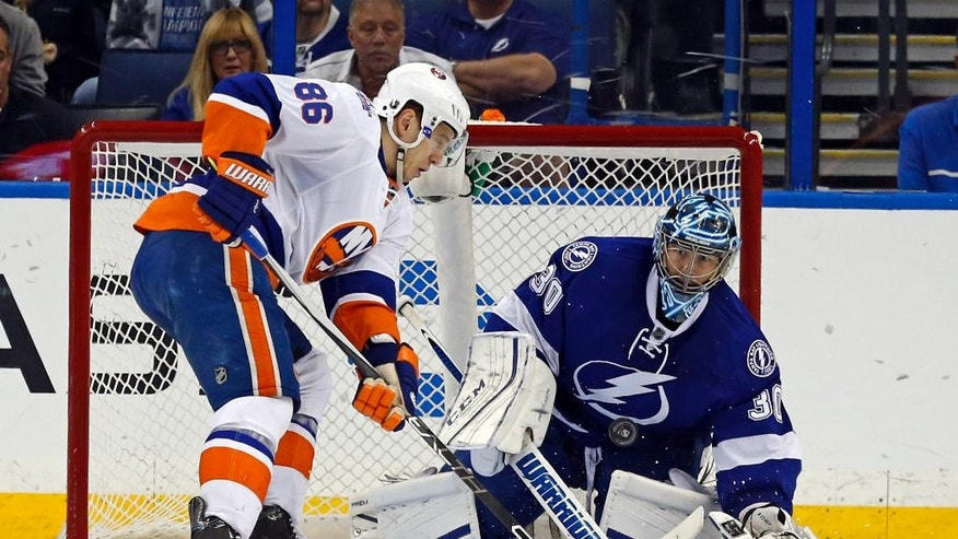 Tampa Bay Lightning goalie Ben Bishop and New York Islanders' Nikolay Kulemin, of Russia, look for a rebound during the second period of an NHL hockey game Friday, March 25, 2016, in Tampa, Fla. (AP Photo/Mike Carlson)