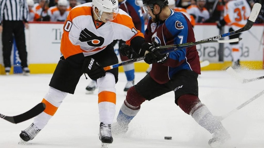 Philadelphia Flyers center Brayden Schenn, left, fights for control of the puck with Colorado Avalanche center John Mitchell in the second period of an NHL hockey game Thursday, March 24, 2016, in Denver. (AP Photo/David Zalubowski)