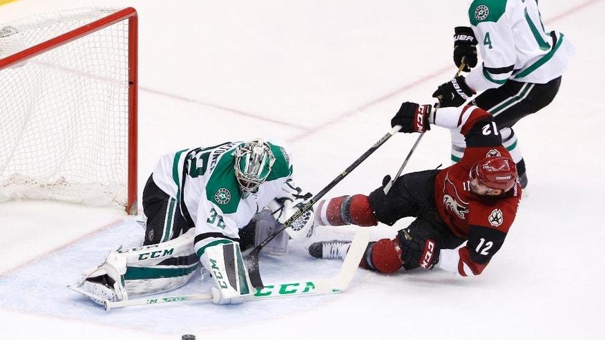 Arizona Coyotes' Brad Richardson (12) gets pulled down by Dallas Stars' Jamie Benn, top right, as he tries to get off a shot on Stars' Kari Lehtonen, left, of Finland, during the second period of an NHL hockey game Thursday, March 24, 2016, in Glendale, Ariz. The Stars' Benn was penalized on the play. (AP Photo/Ross D. Franklin)