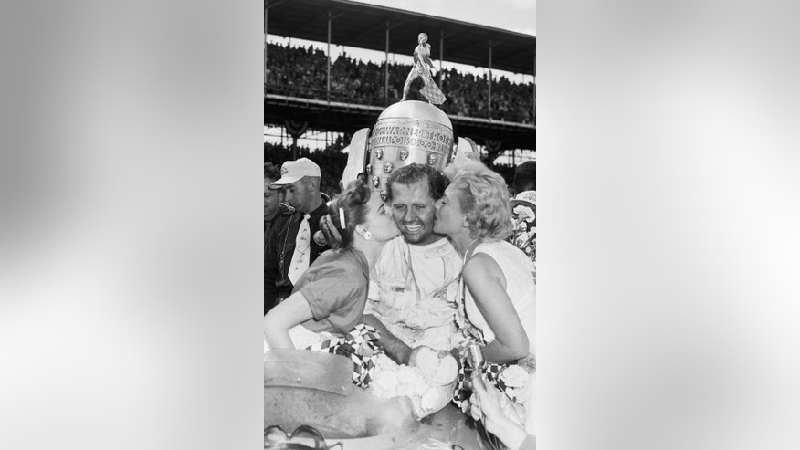 FILE - In this May 30, 1955, file photo, Bob Sweikert receives kisses from his wife, Dolores, left, and singer Dinah Shore after winning the 39th Indianapolis 500 auto race at Indianapolis Motor Speedway in Indianapolis, Ind. (AP Photo/File)