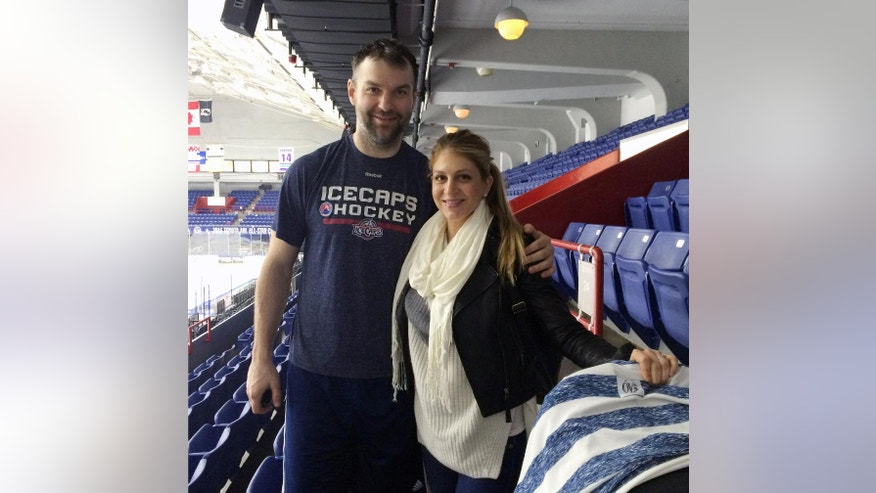 In this Sunday, March 20, 2016 photo, St. John's IceCaps hockey player John Scott and his wife, Danielle, pose after an AHL hockey match against Syracuse, in Syracuse, N.Y. The journeyman tough guy who won the hockey world over in becoming the NHL All-Star Game MVP is having a blast playing in the American Hockey League's eastern-most outpost. (AP Photo/John Wawrow)