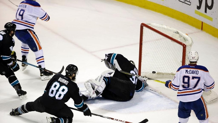 Edmonton Oilers' Patrick Maroon, top left, scores past San Jose Sharks goalie James Reimer, center, during the second period of an NHL hockey game Thursday, March 24, 2016, in San Jose, Calif. (AP Photo/Marcio Jose Sanchez)