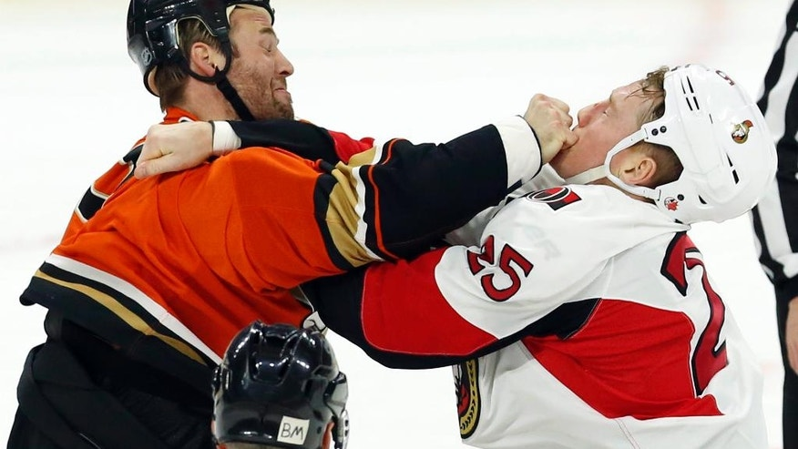 Ottawa Senators' Chris Neil (25) fights with Anaheim Ducks' Clayton Stoner (3) during the first period of an NHL hockey game Saturday, March 26, 2016, in Ottawa, Ontario. (Fred Chartrand/The Canadian Press via AP)