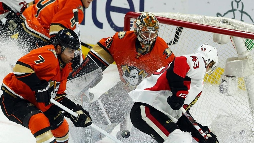 Ottawa Senators' Ryan Dzingel (43) and Anaheim Ducks' Andrew Cogliano (7) and Frederik Andersenn (31) try to gain control of a loose puck during the second period of an NHL hockey game Saturday, March 26, 2016, in Ottawa, Ontario. (Fred Chartrand/The Canadian Press via AP)
