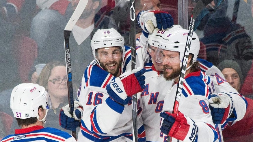 New York Rangers' Chris Kreider, center, celebrates with teammates Derick Brassard (16), Kevin Klein (8) and Ryan McDonagh (27) after scoring against the Montreal Canadiens during the second period of an NHL hockey game, Saturday, March 26, 2016 in Montreal.  (Graham Hughes/The Canadian Press via AP) MANDATORY CREDIT