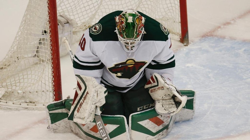 Minnesota Wild goalie Devan Dubnyk makes a save against the Colorado Avalanche in the first period of an NHL hockey game Saturday, March 26, 2016, in Denver. (AP Photo/David Zalubowski)