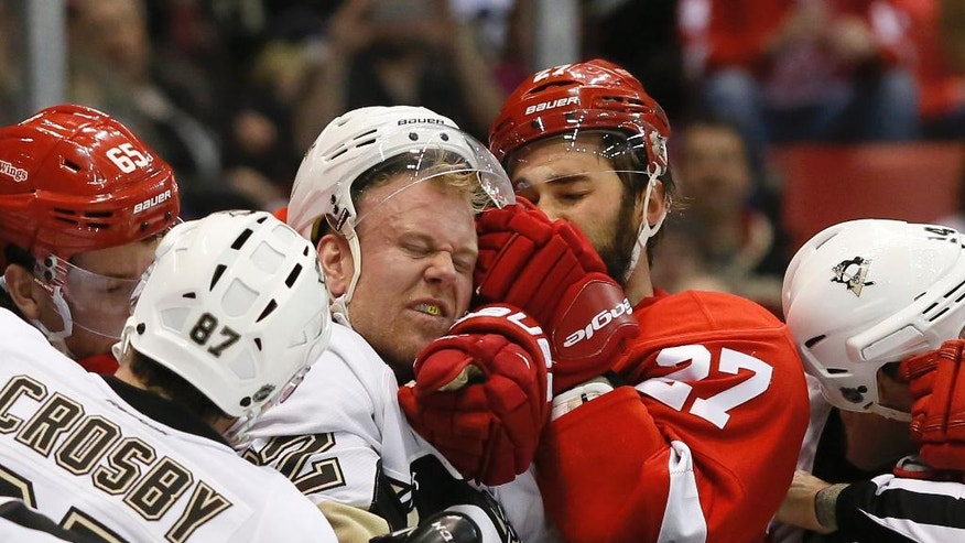 Pittsburgh Penguins' Patric Hornqvist, of Sweden, tangles with Detroit Red Wings' Kyle Quincey (27) around the net during the first period of an NHL hockey game Saturday, March 26, 2016, in Detroit. (AP Photo/Duane Burleson)