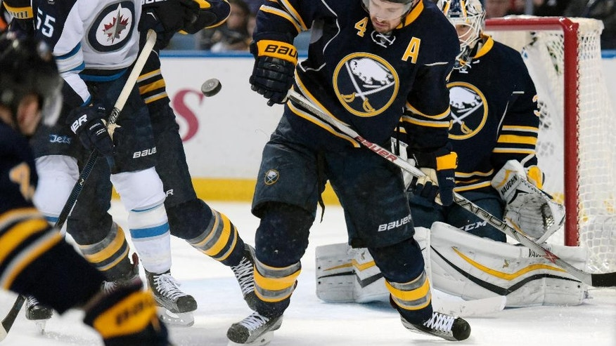 Winnipeg Jets center Mark Scheifele (55) battles for a loose puck with Buffalo Sabres defenseman Josh Gorges (4) in front of goaltender Chad Johnson, right, during the second period of an NHL hockey game, Saturday, March 26, 2016, in Buffalo, N.Y. (AP Photo/Gary Wiepert)