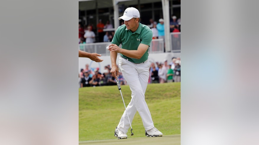 Jordan Spieth hands hit ball to his caddie on the 15th hole during the round of 16 play against Louis Oosthuizen at the Dell Match Play Championship golf tournament at Austin County Club, Saturday, March 26, 2016, in Austin, Texas. (AP Photo/Eric Gay)