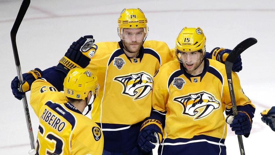Nashville Predators defenseman Mattias Ekholm (14), of Sweden, is congratulated by Mike Ribeiro (63) and Craig Smith (15) after Ekholm scored a goal against the Columbus Blue Jackets in the first period of an NHL hockey game Saturday, March 26, 2016, in Nashville, Tenn. (AP Photo/Mark Humphrey)