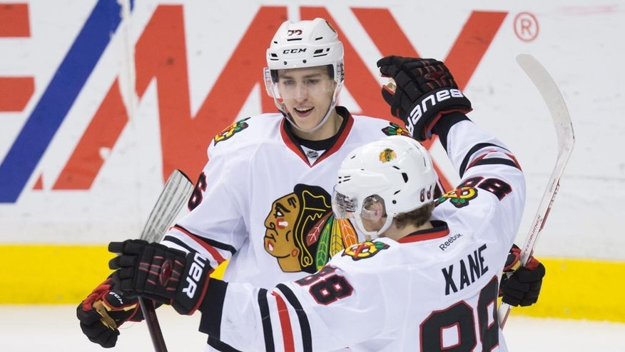 Chicago Blackhawks' Teuvo Teravainen, left, of Finland, and Patrick Kane celebrate Teravainen's goal against the Vancouver Canucks during the third period of an NHL hockey game in Vancouver, British Columbia, Sunday, March 27, 2016. (Darryl Dyck/The Canadian Press via AP)