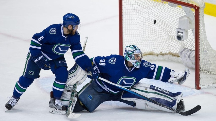 Vancouver Canucks' goalie Ryan Miller, right, allows a goal to Chicago Blackhawks' Teuvo Teravainen (not shown) as teammate Yannick Weber, of Switzerland, watches during the third period of an NHL hockey game in Vancouver, British Columbia, Sunday, March 27, 2016. (Darryl Dyck/The Canadian Press via AP)