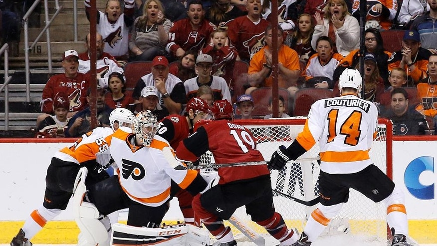 Arizona Coyotes' Shane Doan (19) beats Philadelphia Flyers goalie Steve Mason, second from left, for a goal as Flyers' Sean Couturier (14) defends while Flyers' Nick Schultz (55) works against Coyotes' Antoine Vermette (50) during the second period of an NHL hockey game Saturday, March 26, 2016, in Glendale, Ariz. (AP Photo/Ross D. Franklin)