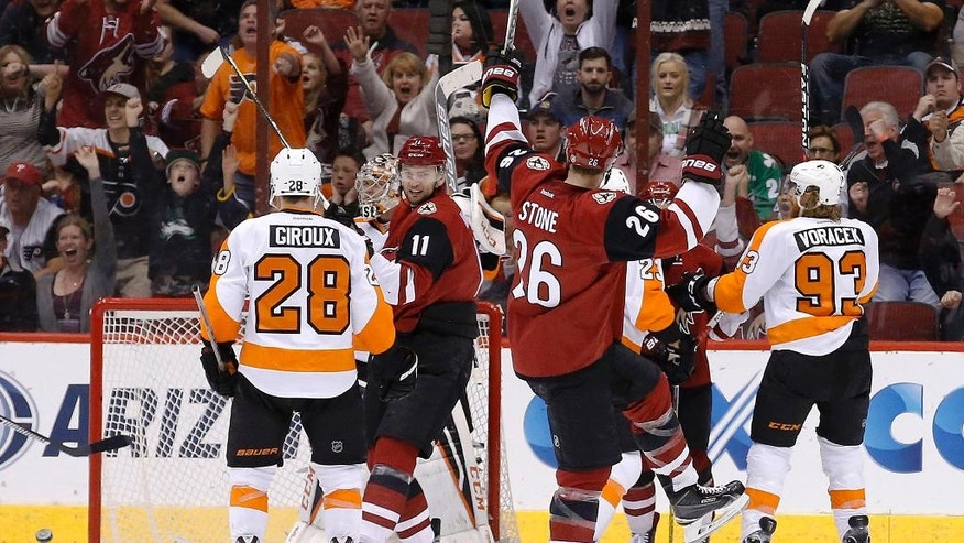 Arizona Coyotes' Michael Stone (26) celebrates his goal as teammate Martin Hanzal (11), of the Czech Republic, smiles at Stone while Philadelphia Flyers' Claude Giroux (28) and Jakub Voracek (93), of the Czech Republic, look for the puck during the second period of an NHL hockey game Saturday, March 26, 2016, in Glendale, Ariz. (AP Photo/Ross D. Franklin)