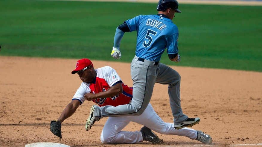 Cuba's Alexander Malleta dives for first base, too late to stop Tampa Bay Rays' Brandon Guyer during a game between the Rays and Cuba's national baseball team in Havana, Cuba, Tuesday, March 22, 2016. President Barack Obama and his family watched the game with Cuba's President Raul Castro, then left early for the airport where the first family departed for Argentina. Tampa Bay defeated Cuba 4-1. (AP Photo/Rebecca Blackwell)