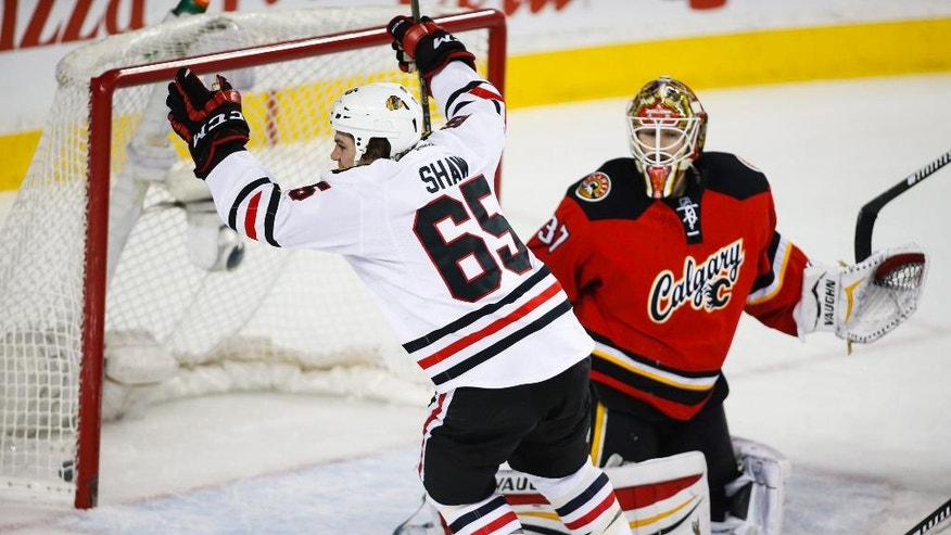 Chicago Blackhawks' Andrew Shaw, left, celebrates his goal as Calgary Flames goalie Joni Ortio, from Finland, looks on during second period NHL hockey action in Calgary, Saturday, March 26, 2016. (Jeff McIntosh/The Canadian Press via AP)