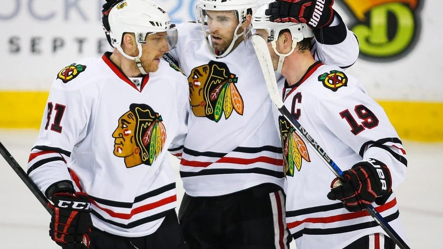 Chicago Blackhawks' Andrew Ladd, centre, celebrates his goal with teammates Marian Hossa, left, of Slovakia, and Jonathan Toews during third period NHL hockey action aainst the Calgary Flames in Calgary, Saturday, March 26, 2016.(Jeff McIntosh/The Canadian Press via AP)