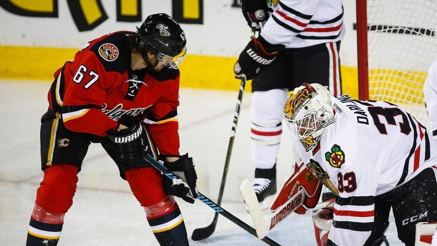 Chicago Blackhawks goalie Scott Darling, right, grabs the puck from Calgary Flames' Michael Frolik, from the Czech Republic, during second period NHL hockey action in Calgary, Saturday, March 26, 2016. (Jeff McIntosh/The Canadian Press via AP)