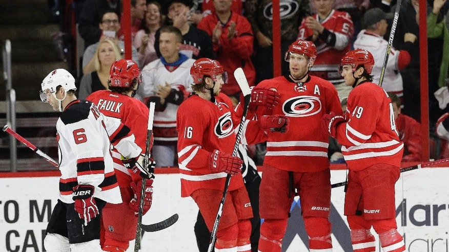 New Jersey Devils' Andy Greene (6) skates away as Carolina Hurricanes' Elias Lindholm (16), of Sweden, Jordan Staal and Victor Rask (49) celebrate Rask's goal during the first period of an NHL hockey game in Raleigh, N.C., Sunday, March 27, 2016. Carolina won 3-2. (AP Photo/Gerry Broome)