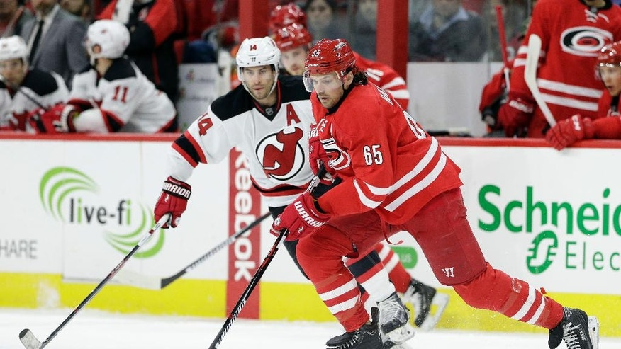 New Jersey Devils' Adam Henrique (14) defends Carolina Hurricanes' Ron Hainsey (65) during the first period of an NHL hockey game in Raleigh, N.C., Sunday, March 27, 2016. (AP Photo/Gerry Broome)