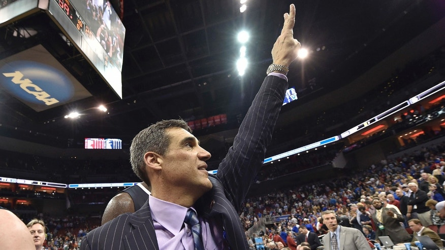 Villanova head coach Jay Wright raises his hand to fans after a regional final men's college basketball game in the NCAA Tournament against Kansas, Saturday, March 26, 2016, in Louisville, Ky.